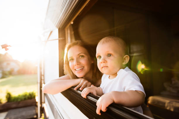 mother and baby son in a camper van. - camping stock photos and pictures