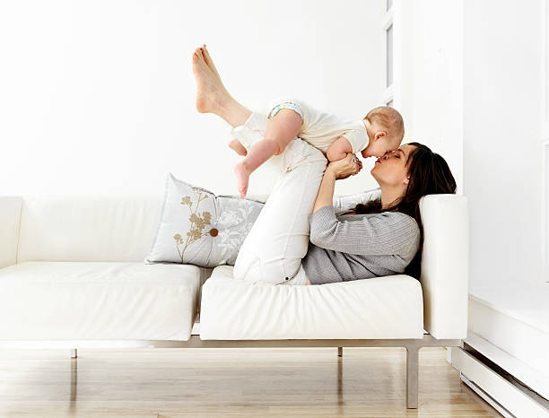 Mother and baby son on couch stock photo