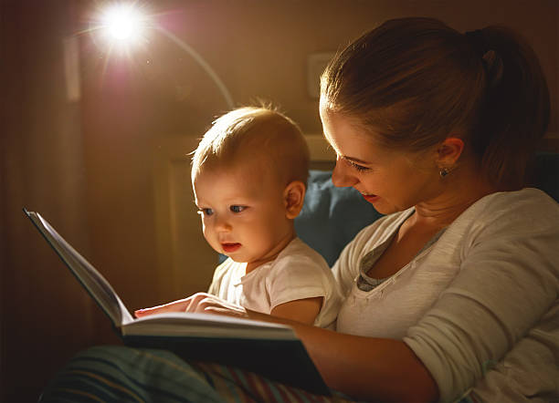 mother and baby son reading a book in bed stock photo