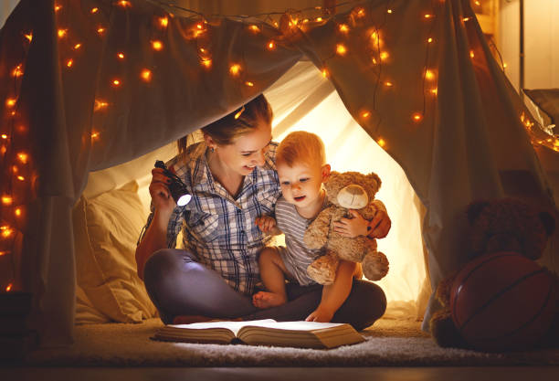 mother and baby son with a book and a flashlight before going to bed - kinder lesezelt stock-fotos und bilder