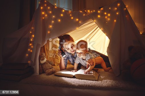 istock mother and baby son with a book and a flashlight before going to bed 673112856