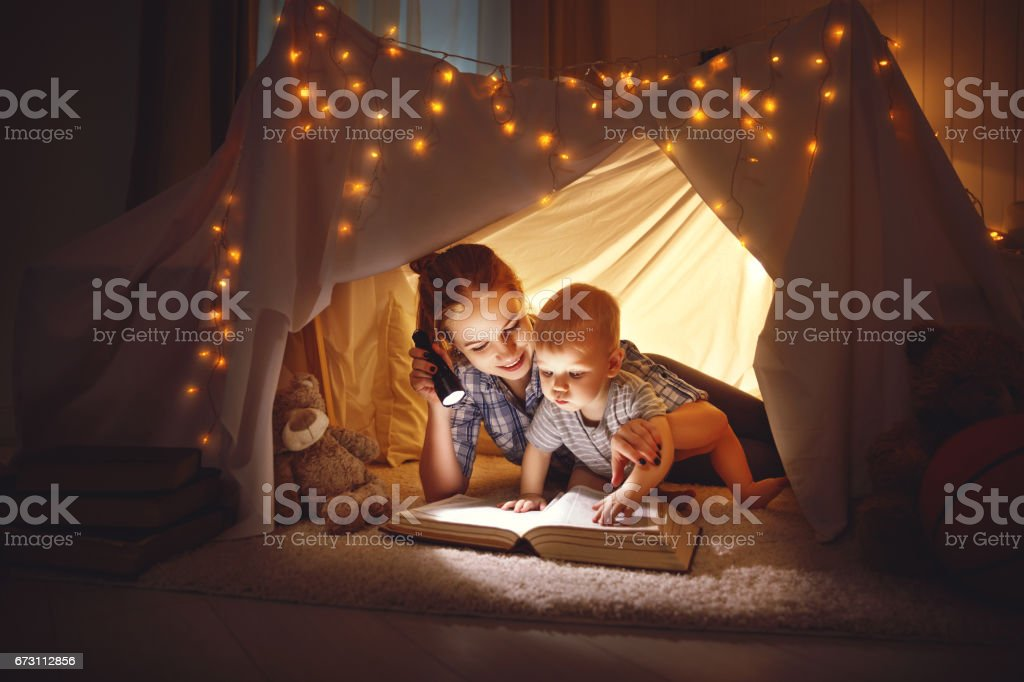mother and baby son with a book and a flashlight before going to bed stock photo