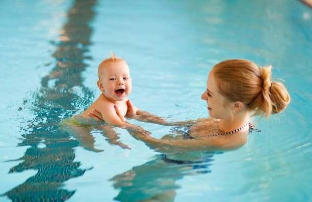 Mother and baby swim  in pool stock photo
