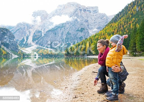 istock Mother and baby throwing stones on lake braies, italy 535969483