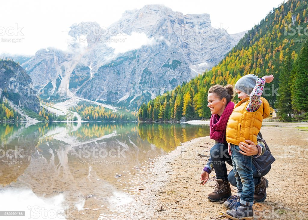 Mother and baby throwing stones on lake braies, italy stock photo