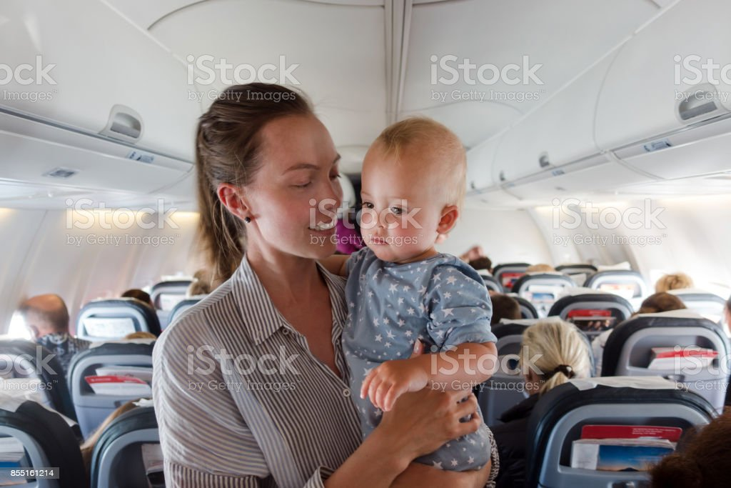 Mother and baby traveling on plane stock photo