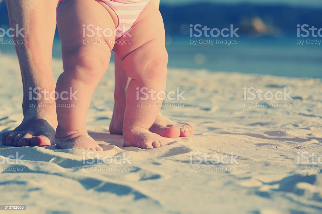 Mother and baby walking on sand beach stock photo
