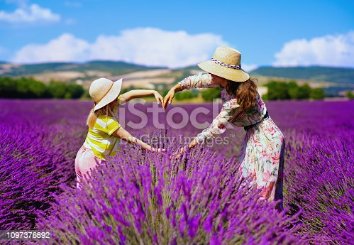 trendy mother and child making heart with hands at lavender field in Provence, France. Provence's best scenery inspire mother and child to get memorable love shot while spending time here in summer