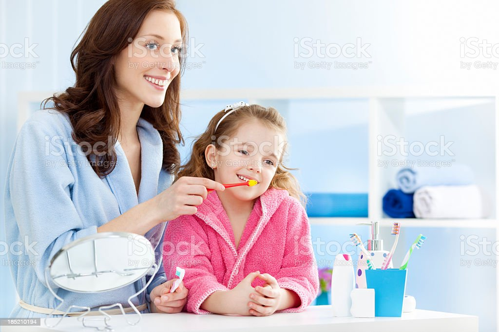 Mother and child brushing teeth together. royalty-free stock photo