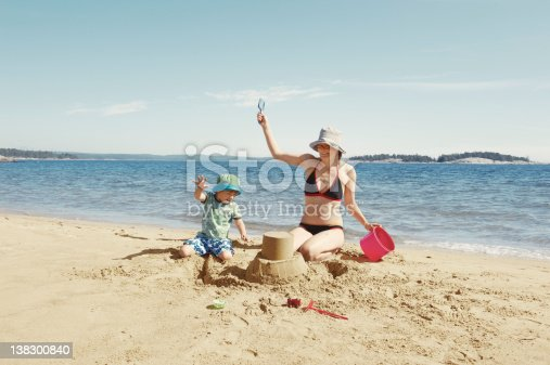 istock Mother and child building sandcastle 138300840