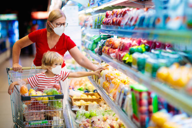Mother and child buying fruit in supermarket. Shopping with kids during virus outbreak. Mother and child wearing surgical face mask buying fruit in supermarket. Mom and little boy buy fresh vegetable in grocery store. Family in shop. supermarket stock pictures, royalty-free photos & images