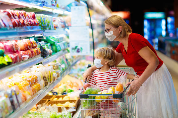 Mother and child buying fruit in supermarket. stock photo