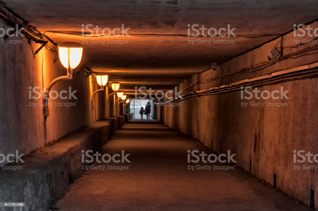 Mother and child crossing a subterranean passage stock photo