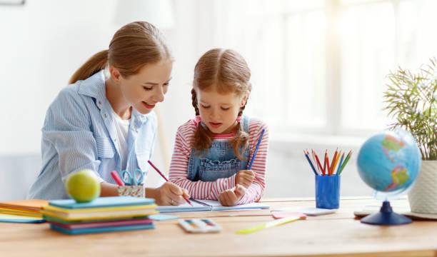 Mutter und Kind Tochter beim Schreiben und Lesen zu Hause – Foto