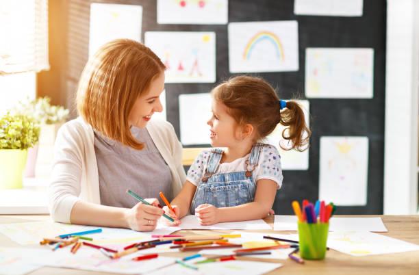 母親和孩子的女兒在幼稚園的創造力繪製 - kids drawing 個照片及圖片檔