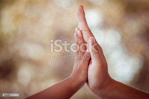 istock mother and child daughter making hi five gesture 677133660