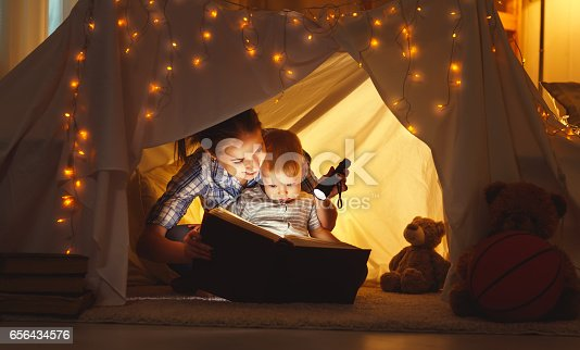 istock mother and child daughter with a book and a flashlight before going to bed 656434576