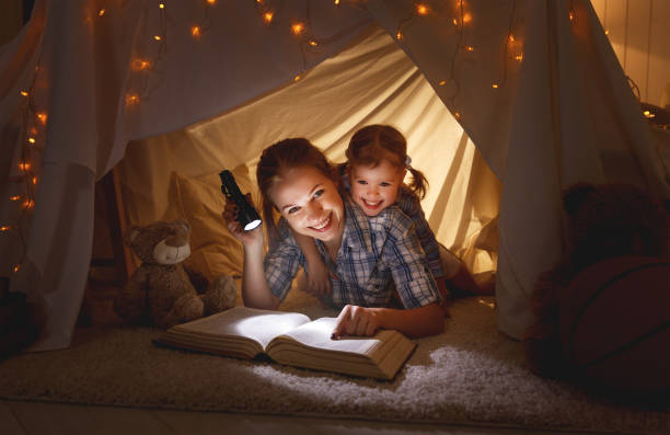 mother and child daughter with a book and a flashlight before going to bed - kinder lesezelt stock-fotos und bilder