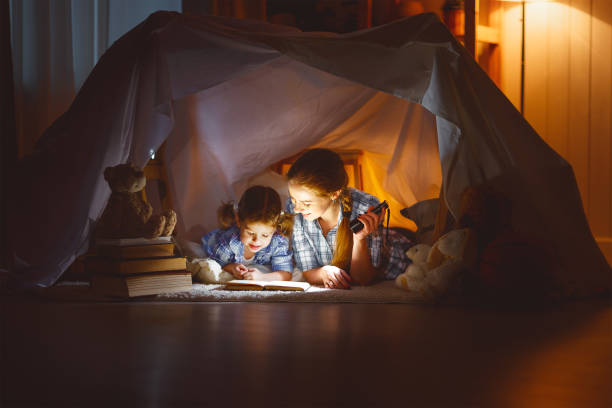mother and child daughter with a book and a flashlight before going to bed - deckenleuchte kinderzimmer stock-fotos und bilder