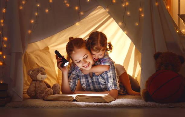 tochter von mutter und kind mit einem buch und einer taschenlampe vor dem schlafengehen - deckenleuchte kinderzimmer stock-fotos und bilder