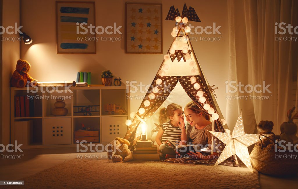 mother and child daughter with a book and a flashlight before going to bed stock photo