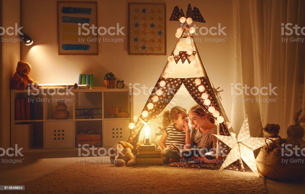 filha de mãe e filho com um livro e uma lanterna antes de ir para a cama - foto de acervo