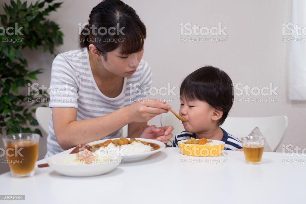 mother and child eating curry rice stock photo