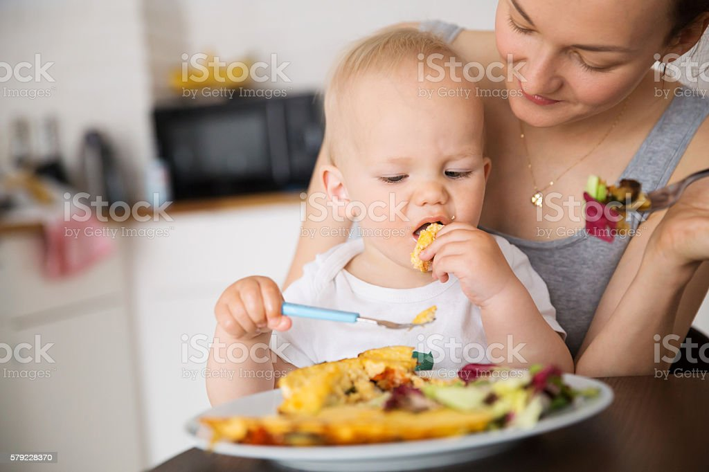 Mother and child eating together​​​ foto