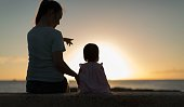 Mom showing her young daughter the sunset on the beach. Happy family.