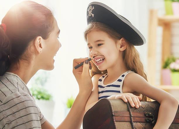 mother and child girl playing - matrosin kostüm stock-fotos und bilder