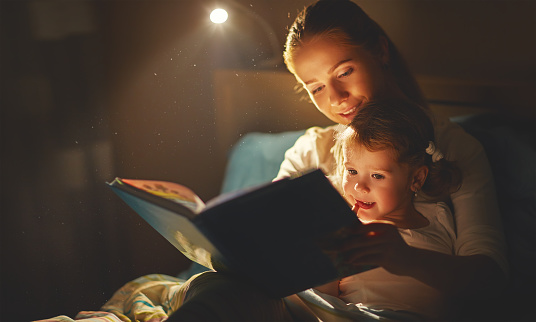 mother and child girl reading a book in bed