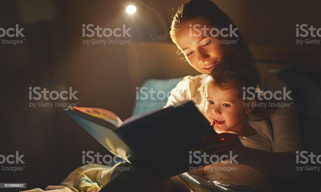 mother and child girl reading a book in bed stock photo