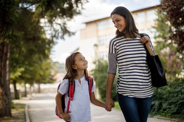 Mother and child going home from school stock photo