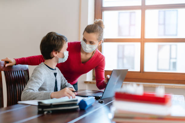 Mother and child having e-learning session with teacher during crisis stock photo