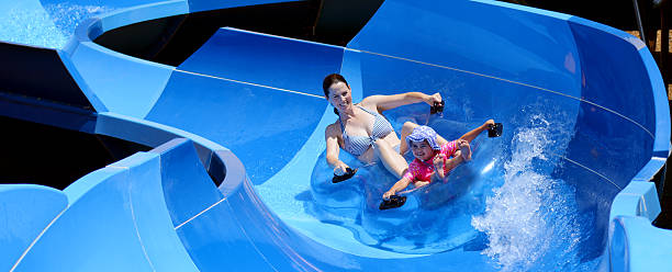Mother and child having fun in water park stock photo