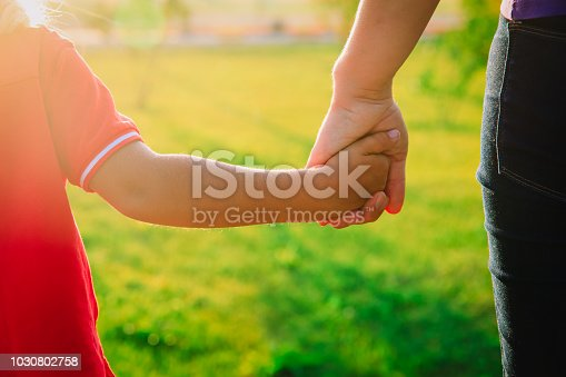 mother and child holding hands at sunset city, parenting