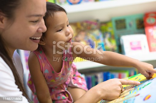 istock Mother and child looking picture books together. Family time. 1145771850