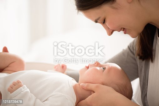 909771884 istock photo Mother and child on a bed. Mom and baby boy in diaper playing in sunny bedroom. 1213725478