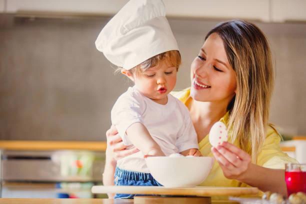 mutter und kind malen eier für den osterurlaub - schöne osterbilder stock-fotos und bilder