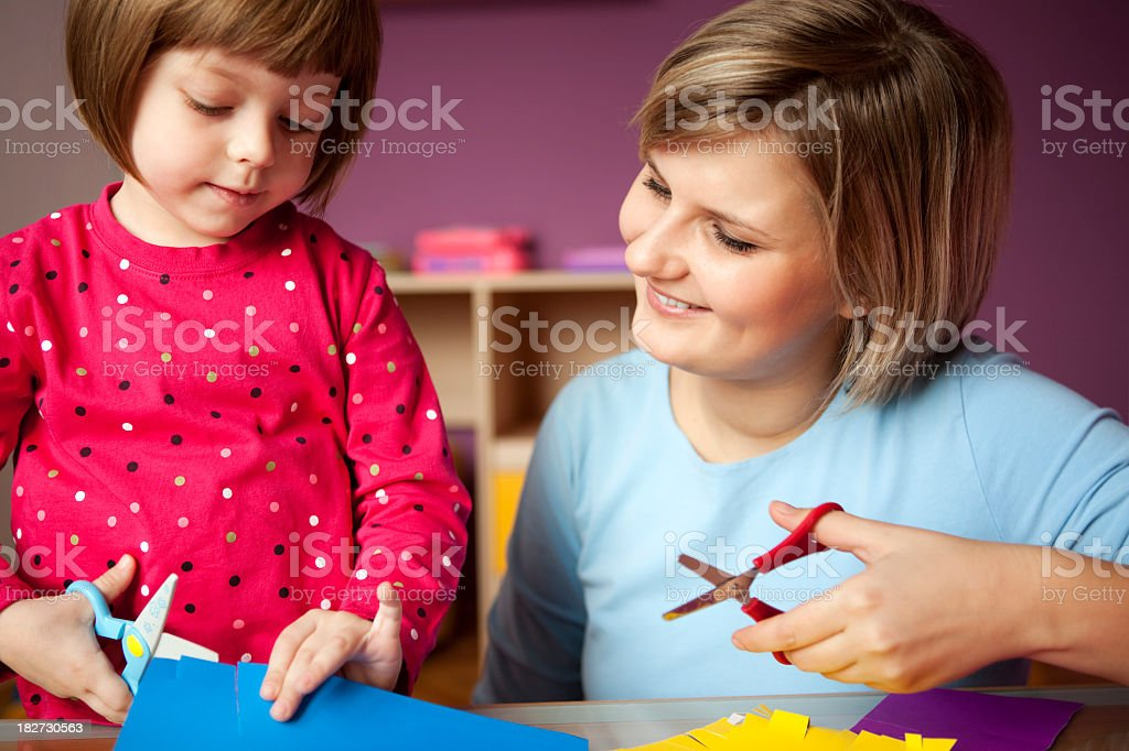Mother and child play with scissors and construction paper stock photo