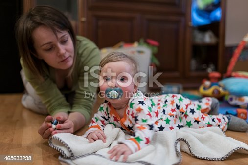 istock Mother and child playing on the floor 465633238