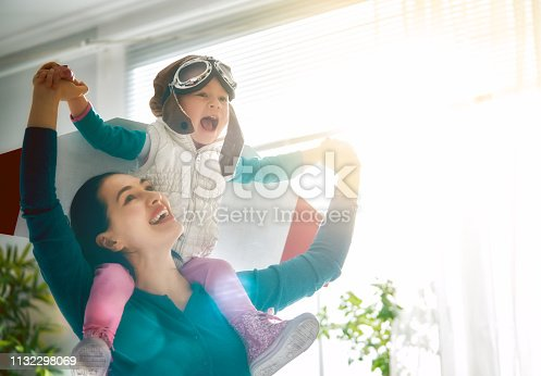 Happy family is having fun at home. Mother and her child girl playing together. Girl in pilot's costume.