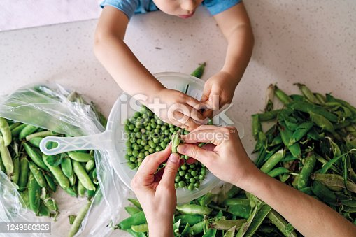 Mother and child preparing green pea at kitchen together