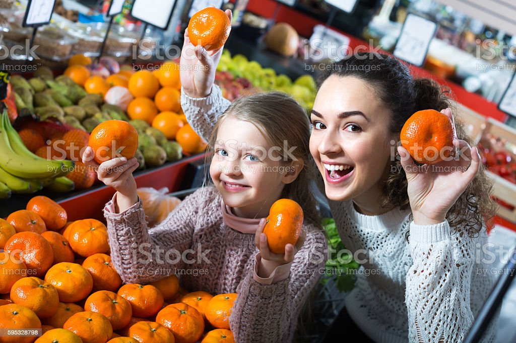 Cheerful young woman and cute little girl selecting sweet tangerines...