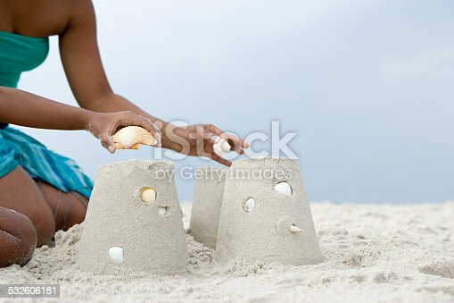 istock Mother and child putting shells on sandcastles 532606181