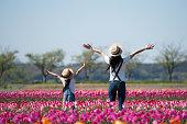 花の畑で手を上げている母子