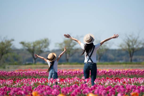 花の畑で手を上げている母子 - ライフスタイル ストックフォトと画像