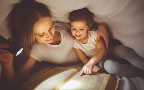 mother and child read book under blanket with a flashlight - deckenleuchte kinderzimmer stock-fotos und bilder