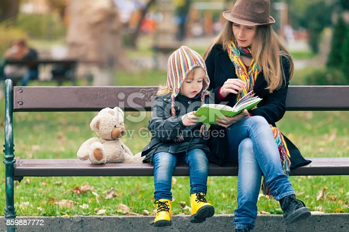 Mother and her little child reading a book in autumn park.