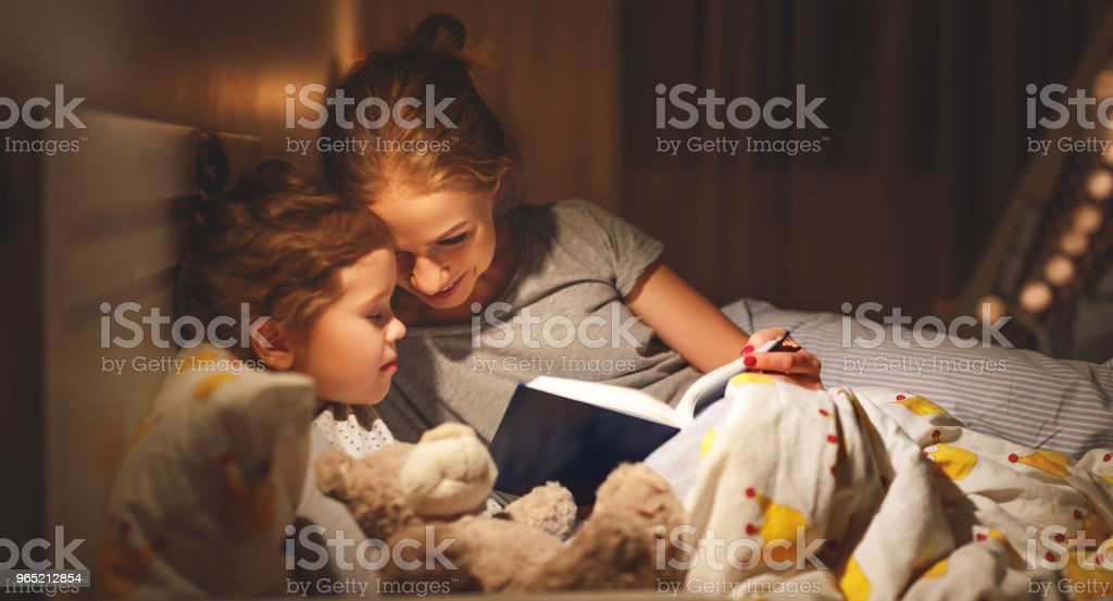 mother and child reading book in bed before going to sleep zbiór zdjęć royalty-free